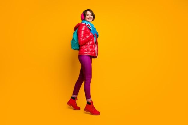 Foto di profilo a figura intera di bella signora escursionismo hobby andando in montagna con gruppo turistico indossare stivali cappotto rosso casual guanti sciarpa blu copri orecchie pantaloni