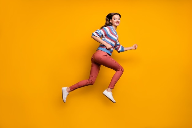 Foto laterale di profilo integrale della ragazza allegra che salta veloce