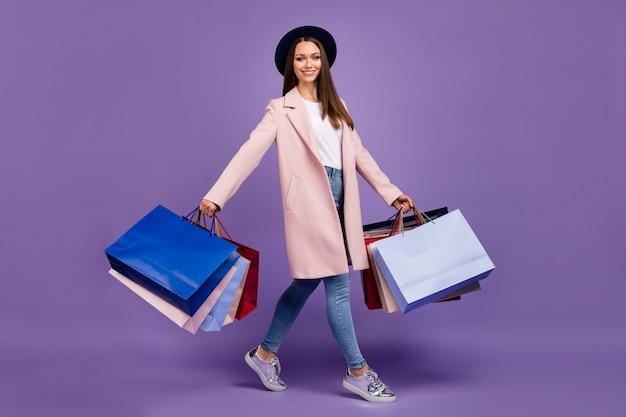 Foto di profilo a figura intera di una ragazza allegra adorabile alla moda tenere molte borse andare dal centro commerciale indossare abbigliamento beige denim copricapo scarpe da ginnastica isolate su sfondo di colore viola