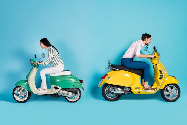 Foto laterale del profilo a figura intera del marito moglie funky pazza desidera che l'elicottero di guida della competizione sportiva goda di abbigliamento formale ad alta velocità con movimento ad alta velocità isolato sopra la parete di colore blu