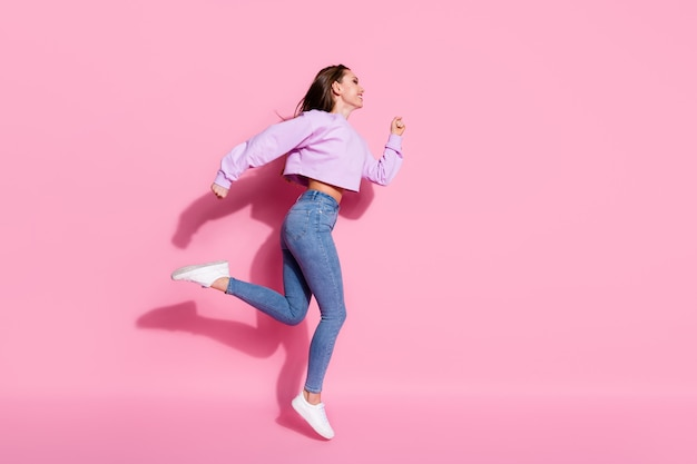 Foto laterale del profilo a tutta lunghezza di una ragazza energica che salta correndo dopo gli sconti di stagione indossa scarpe da ginnastica in stile elegante e alla moda per giovani isolate su uno sfondo di colore pastello