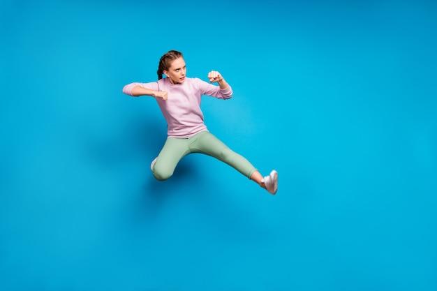 Foto laterale del profilo integrale della ragazza sportiva concentrata allenare le sue abilità di kick boxing saltare combattere i nemici indossare scarpe da ginnastica bianche vestito elegante isolate su sfondo di colore blu
