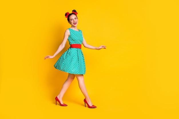 La foto a lato del profilo a tutta lunghezza di una bella ragazza va a copyspace indossa abiti turchesi isolati su uno sfondo di colore brillante