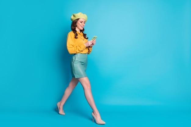 Foto laterale del profilo a tutta lunghezza della ragazza positiva andare a piedi copyspace utilizzare il blog dello smartphone indossare tacchi a spillo gialli copricapo isolate su sfondo blu