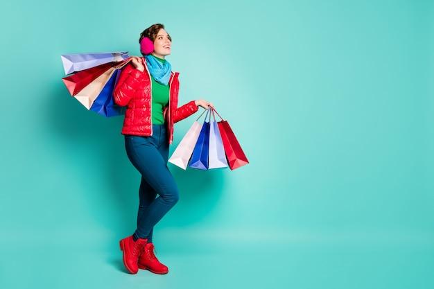 Profilo a figura intera foto laterale positiva ragazza centro commerciale cliente tenere borse guardare copyspace sogno off-sales indossare maglione verde rosa rosso pantaloni blu pantaloni isolati verde acqua muro di colore