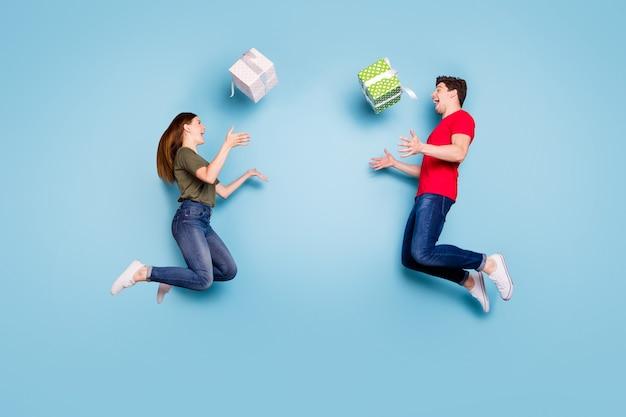 Foto laterale di profilo integrale di due studenti pazzi sposati festeggiano il 14 febbraio salto vacanza lancio confezione regalo abbigliamento casual stile casual scarpe da ginnastica isolato sfondo blu