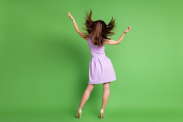 La parte posteriore a tutta lunghezza guarda la foto di una signora abbastanza alta e snella voltata indietro butta la pettinatura al volo goditi la calda brezza della stagione primaverile indossa un mini abito tacchi a spillo isolato sfondo di colore verde