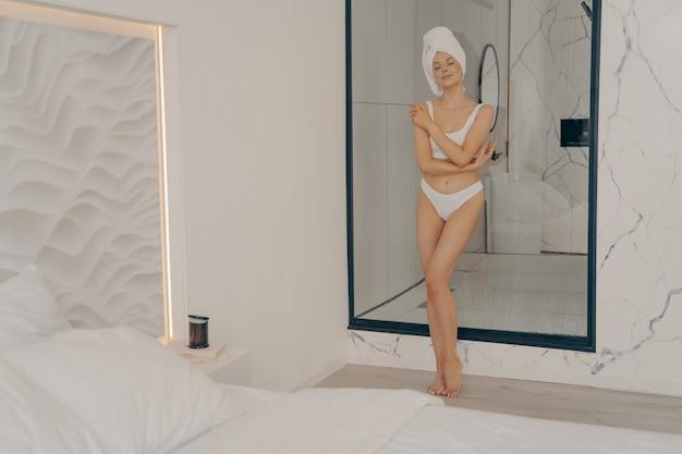 Tutta la lunghezza di una giovane donna snella rilassata con gli occhi chiusi in posa all'interno della camera da letto elegante, in biancheria intima bianca e testa avvolta in un asciugamano da bagno dopo la doccia mattutina. concetto di bellezza e cura del corpo