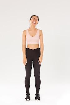 Tutta la lunghezza della ragazza asiatica bruna carina riluttante e piagnucolosa riluttante ad allenarsi, piangere e lamentarsi, sentirsi stanca dopo esercizi di fitness.