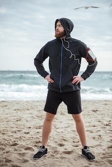 Corridore a figura intera sulla vista frontale della spiaggia che distoglie lo sguardo