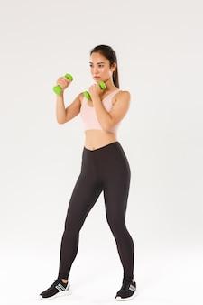 Integrale della sportiva bruna asiatica dall'aspetto serio, atleta femminile in reggiseno sportivo e leggings sollevamento manubri, esercizi di fitness su sfondo bianco.