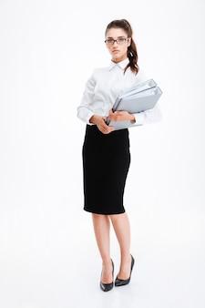 Per tutta la lunghezza di una giovane donna d'affari seria con gli occhiali in piedi e in possesso di cartelle su un muro bianco