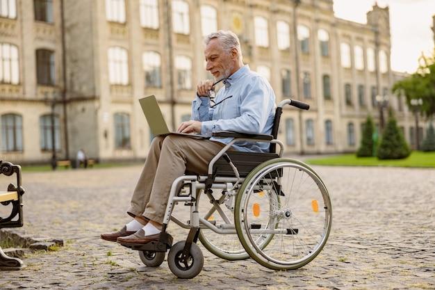 Colpo integrale di uomo maturo impegnato che recupera paziente in sedia a rotelle che lavora su un laptop all'aperto Foto Premium