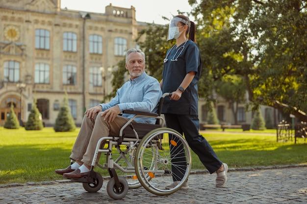 Colpo a figura intera di una giovane infermiera premurosa che indossa una visiera e una maschera che cammina con un paziente uomo maturo