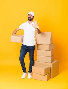 Colpo integrale dell'uomo di consegna fra le scatole sopra giallo isolato che conta cinque con le dita