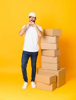 Colpo integrale dell'uomo di consegna fra le scatole sopra giallo isolato che mostra un segno di gesto di silenzio
