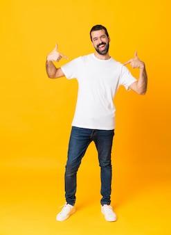Colpo integrale dell'uomo con la barba sopra isolato giallo fiero e soddisfatto di sé