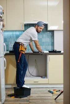 Colpo integrale di un giovane idraulico professionista riparatore che sceglie lo strumento migliore per gli strumenti di lavoro