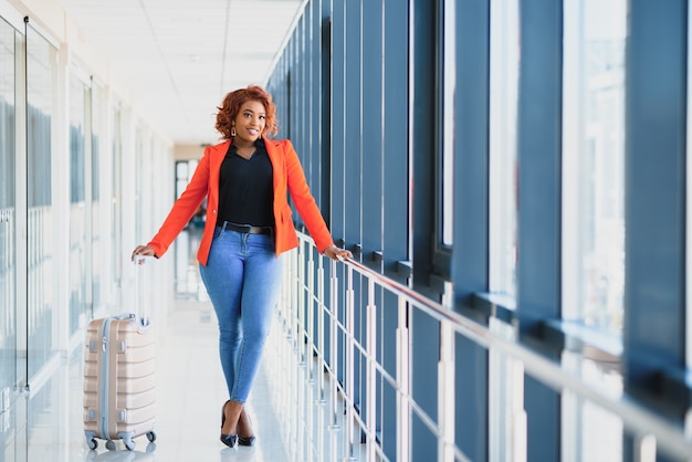 Ritratto laterale integrale di giovane donna di colore che cammina con la valigia in aeroporto