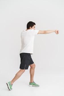 Vista laterale integrale di un giovane sportivo sicuro che fa gli esercizi di boxe sopra bianco