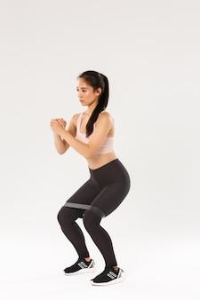 Vista laterale integrale della ragazza asiatica sottile focalizzata che fa allenamento fitness, atleta femminile stringe le mani insieme ed esegue esercizi di squat con banda di resistenza di allungamento, attrezzatura per l'allenamento.