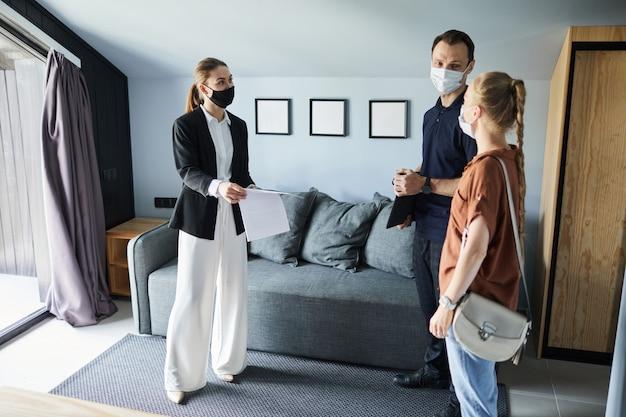 Ritratto di vista laterale a tutta lunghezza dell'agente immobiliare femminile che indossa la maschera mentre firma un contratto con una giovane coppia che acquista una nuova casa, copia spazio