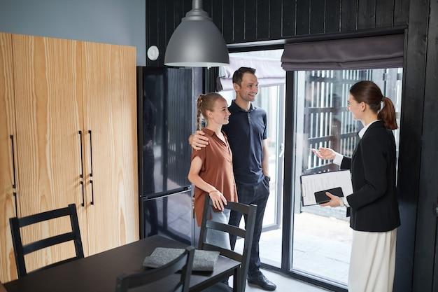 Ritratto a figura intera di giovane coppia che parla con un agente immobiliare mentre acquista una nuova casa, copia spazio