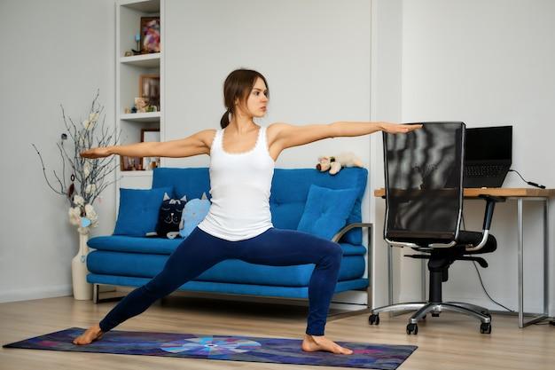 Vista laterale integrale della giovane donna che pratica yoga a casa, in piedi nella posizione del guerriero due