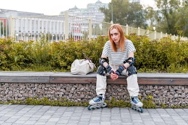 Ritratto di seduta integrale della donna sportiva in pattini a rotelle sulla strada