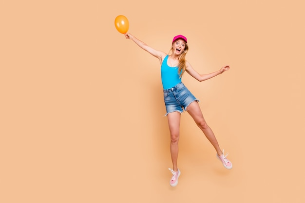 Ritratto integrale del corpo della ragazza emozionante che porta vestito casuale che vola via tenendo il pallone aerostatico giallo