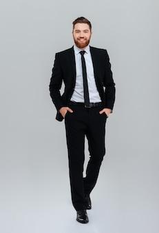 Uomo d'affari barbuto sorridente integrale in abito nero con le mani in tasca