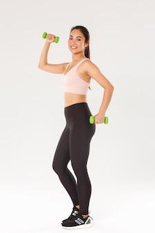 Integrale dell'atleta femminile sorridente, ragazza carina che fa esercizi di fitness con manubri. sportswoman in active wear allenamento in palestra, sfondo bianco.