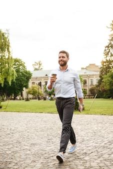 Uomo sorridente integrale in abbigliamento formale, camminando attraverso il parco portando caffè da asporto e laptop d'argento
