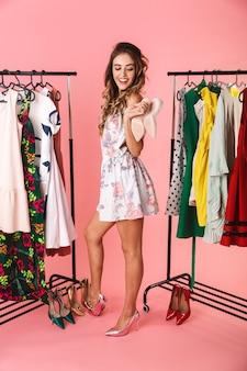 Tutta la lunghezza della donna sorridente in abito in piedi vicino al guardaroba con i vestiti e scegliendo cosa indossare isolato sul rosa