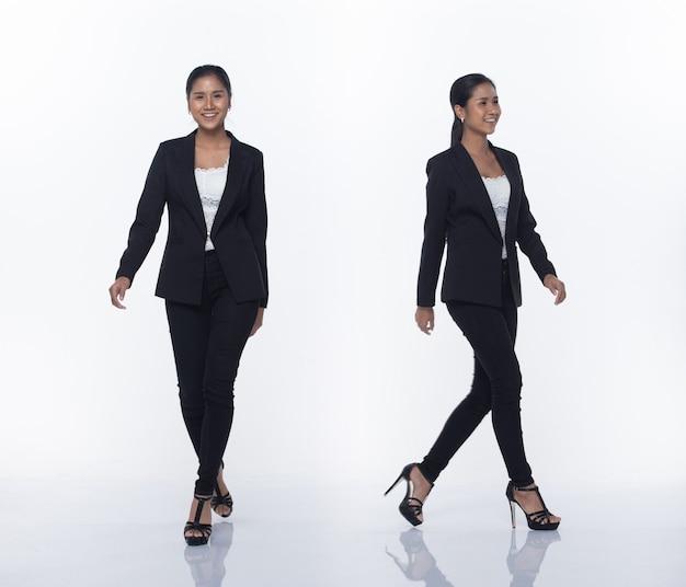 Figura intera a scatto, donna d'affari asiatica in piedi in nero vestito formale pantaloni e scarpe, illuminazione studio sfondo bianco isolato, avvocato capo atto posa sorriso sguardo intelligente camminando tacchi alti