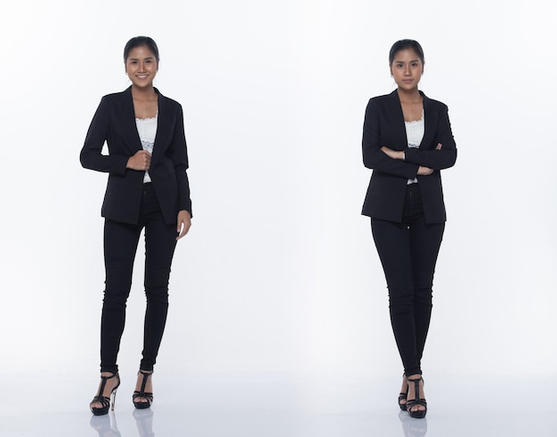 Figura intera a scatto, donna d'affari asiatica in piedi in nero vestito formale adeguato pantaloni e scarpe, illuminazione studio sfondo bianco isolato, avvocato capo atto posa sorriso sguardo intelligente