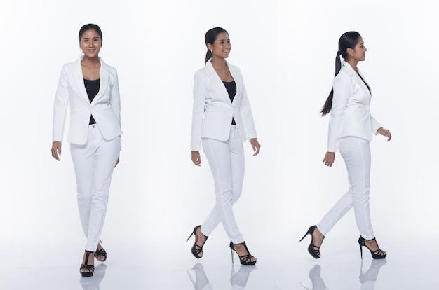 Figura intera a scatto, donna d'affari asiatica in piedi in bianco vestito formale adeguato pantaloni e scarpe, illuminazione studio sfondo bianco isolato, avvocato capo atto posa sorriso sguardo intelligente camminando tacchi alti