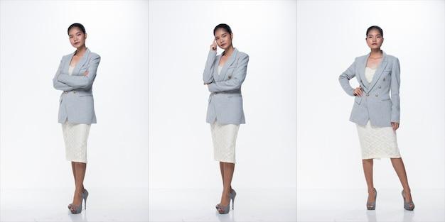 Figura intera a scatto, donna d'affari asiatica in piedi in abito bianco formale adeguato gonna e scarpe con tacco alto, illuminazione da studio sfondo bianco isolato, avvocato capo atto posa sorriso sguardo intelligente
