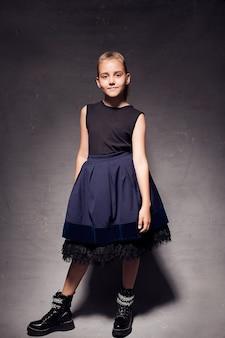 Una foto in studio a figura intera di una bambina di 9-10 anni con una gonna e una giacca vaporose, su uno sfondo scuro. immagini alla moda per i bambini.