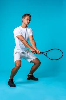 Ritratto integrale dello studio di un uomo del giocatore di tennis sulla fine blu del fondo su