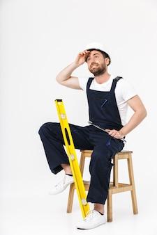 Per tutta la lunghezza di un uomo costruttore barbuto stanco che indossa tute e elmetto protettivo seduto su una sedia isolata su un muro bianco