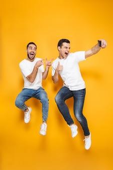 Tutta la lunghezza di due amici uomini eccitati allegri che indossano magliette bianche che saltano isolate sul muro giallo, facendo selfie