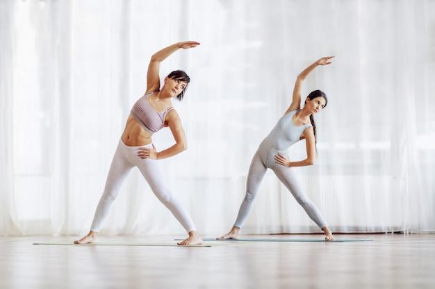 Integrale di due giovani donne magre in forma in piedi con le gambe divise e le mani sui fianchi sul tappetino in studio di yoga.