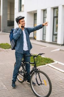 Ritratto verticale a figura intera di allegro bel fattorino di biciclette con zaino termico che parla al telefono cellulare, vede il cliente e segna la posizione alzando la mano.