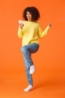 Colpo verticale integrale allegro carino tecnologia dipendente ragazza afro-americana moderna con taglio di capelli afro, saltando e trionfando leggendo grandi notizie da smartphone, arancione
