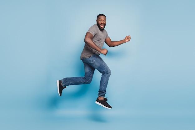 Vista a tutta lunghezza del ragazzo afro che salta correndo isolato su sfondo blu