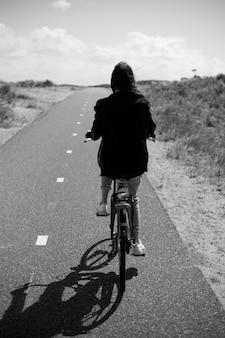 Vista a figura intera. vista posteriore di una giovane ragazza cammina single in bicicletta sulla strada in tempo di giorno pieno di sole. visualizzazione in bianco e nero.