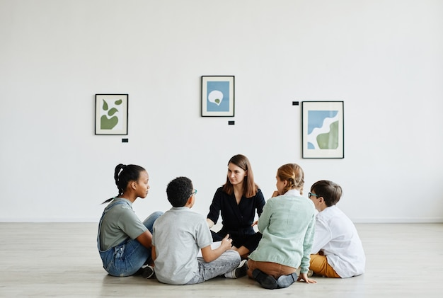 Vista a tutta lunghezza in un gruppo eterogeneo di bambini seduti in cerchio durante la lezione nella galleria d'arte, copia spazio