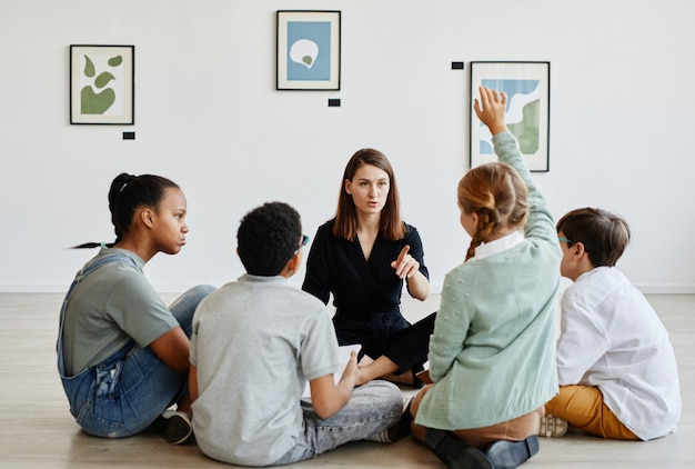 Vista a tutta lunghezza in un gruppo eterogeneo di bambini seduti in cerchio durante la lezione in galleria d'arte con insegnante femminile