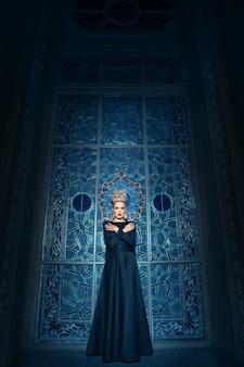 Vista a figura intera di una grande giovane modella bionda, vestita con un lungo abito nero, con acconciatura elegante, grande corona e orecchini.